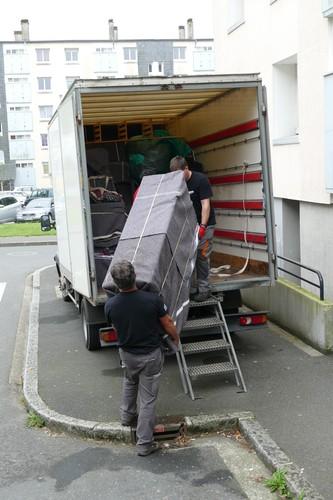 Les aides-déménageurs manipulent un meuble emballé et protégé dans une couvertureides-déménageurs